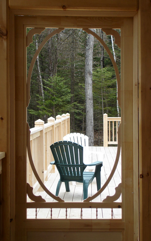 View of chairs on the deck, through decorative screen door.